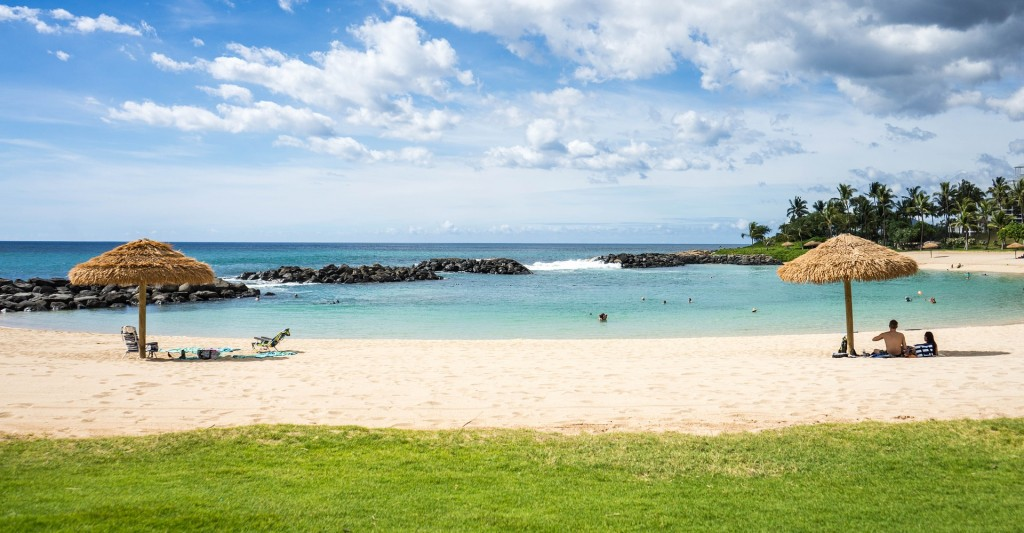 An idyllic beach in Hawaii with two coconut umbrellas - a perfect destination to enjoy with the protection of Travel Insurance