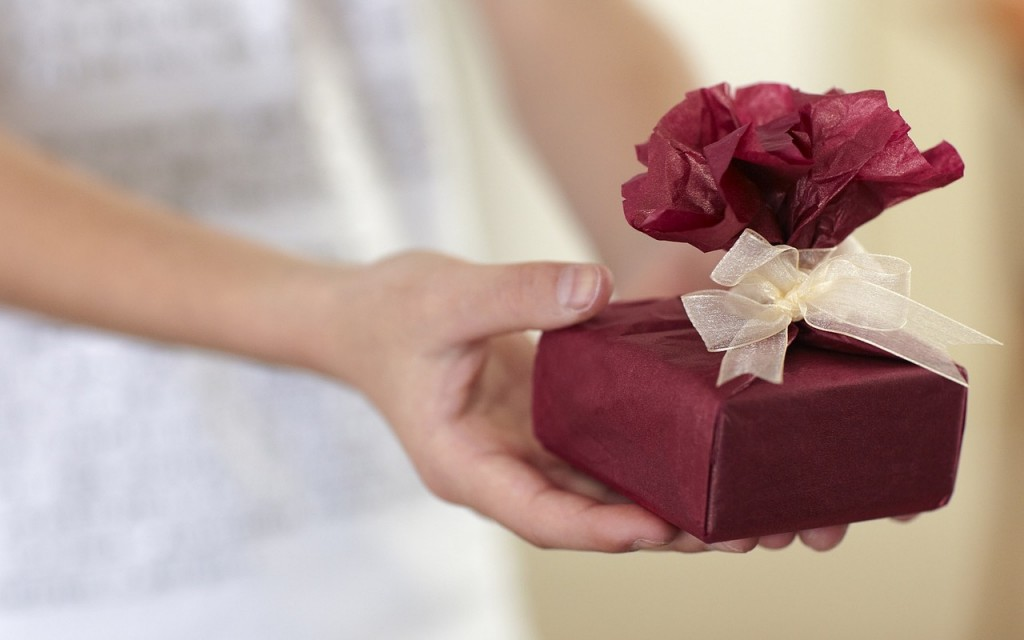 An outstretched hand giving a pretty gift - a small box wrapped in red tissue with a cream ribbon, symbolic of the gift of Health Assessments for Christmas